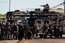 Heavily armed police watch protesters in Ferguson, Mo.