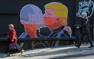 People walk past a mural on a restaurant wall depicting Republican presidential hopeful Donald Trump and Russian President Vladimir Putin greeting each other with an passionate kiss in the Lithuanian capital Vilnius. PETRAS MALUKAS / AFP - Getty Images